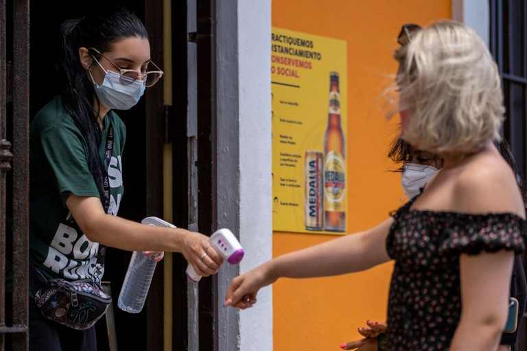 A restaurant hostess checks the temperature of a client with a digital temperature meter at the entrance of a restaurant in Old San Juan