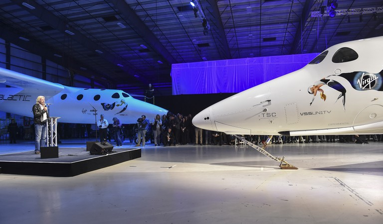 Virgin Galactic's Richard Branson speaks to guest during the roll-out ceremony of the new SpaceShip Two VSS Unity spaceship, right, at the Mojave Air and Space Port on February 19, 2016