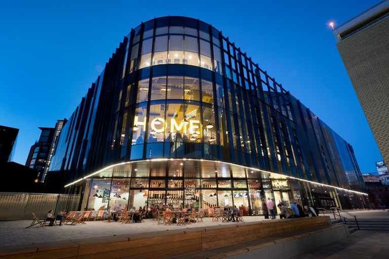 HOME centre for contemporary arts, performance, theatre and film located in Tony Wilson Square, Manchester city centre at night.