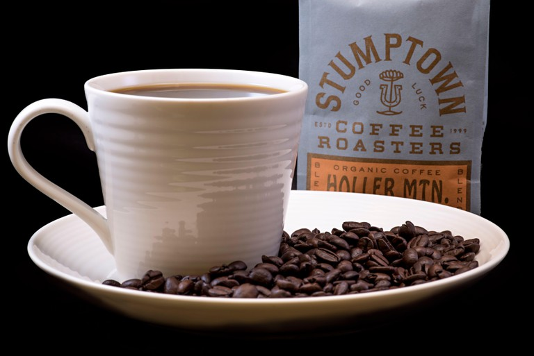 Stumptown Holller Mtn. coffee bag with a cup of Stumptown coffee in a white mug on a white plate with coffee beans and a solid black background