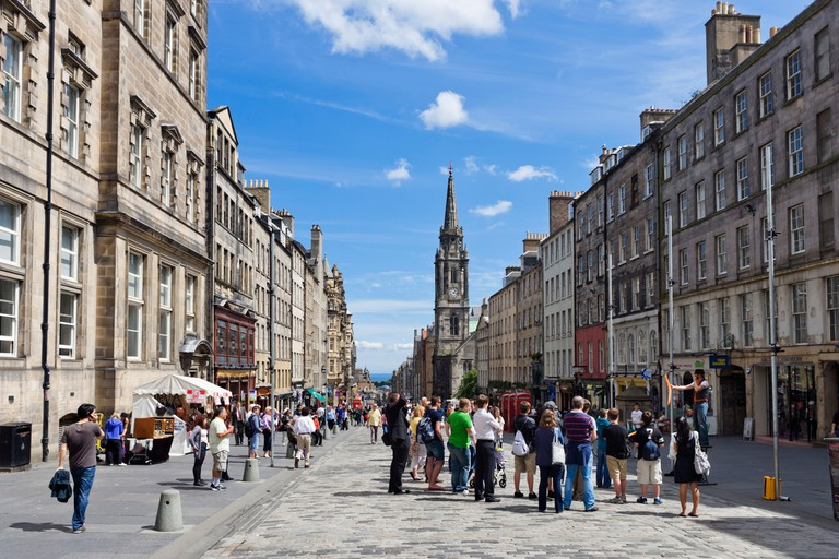 Shops and street entertainer on the High Street looking towards Holyrood, The Royal Mile, Edinburgh, Scotland, UK
