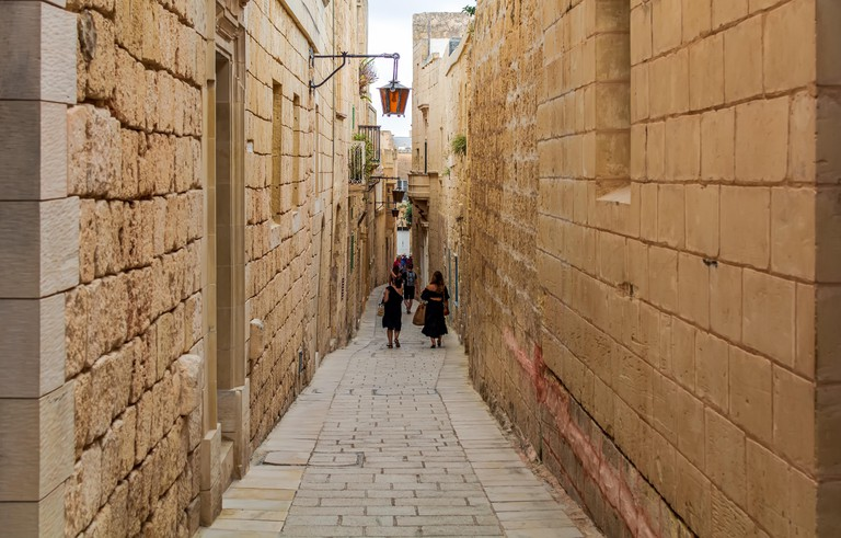 """Tourists wandering along typical narrow medieval street of Mdina, also known as """"Silent city"""", paved with stone slabs"""