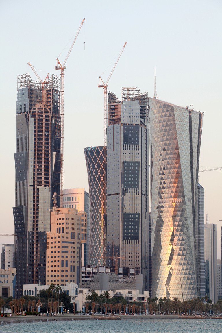 Skyscrapers just behind the Corniche waterfront in Doha, Qatar, nearing completion, are lit by the sunset November 14, 2009