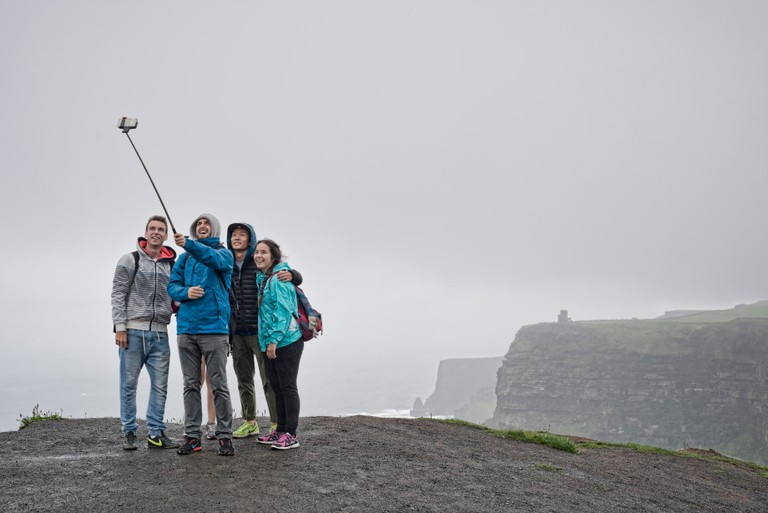 Group of people taking a selfie with a selfie stick at the Cliffs of Moher in Ireland