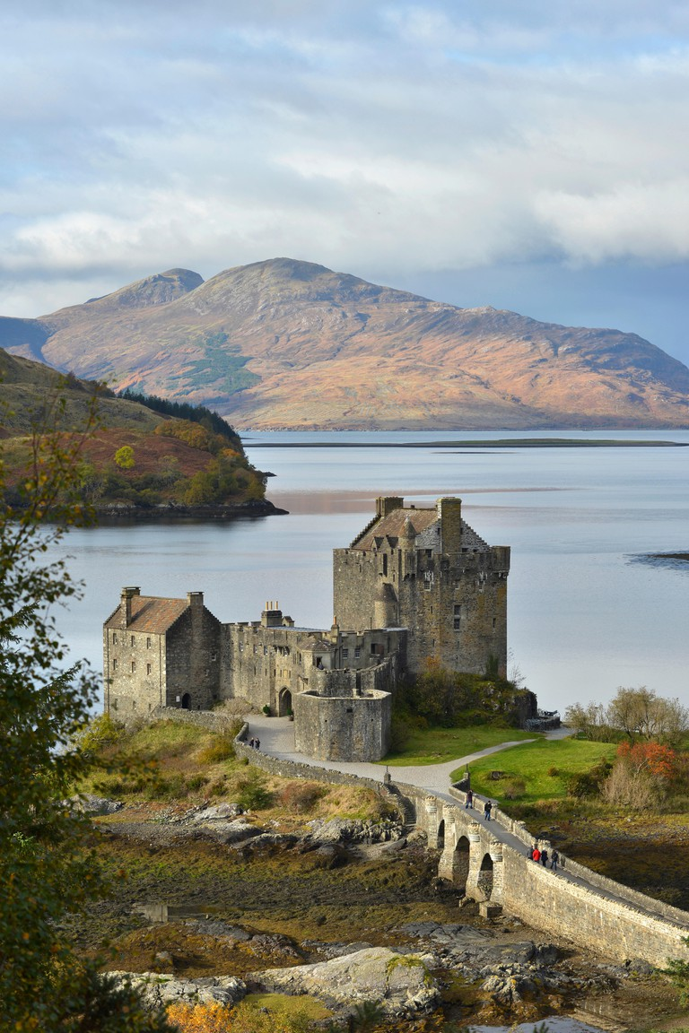 Eilean Donan Castle with autumnal forest, headquarters of the Scottish clan of Macrae, Loch Duich, Dornie, North West Highlands