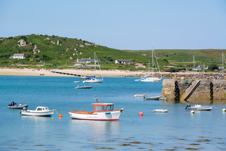Tresco isles of Scilly New Grimsby harbour boats and quay with Bryher island in the background, Cornwall England UK.