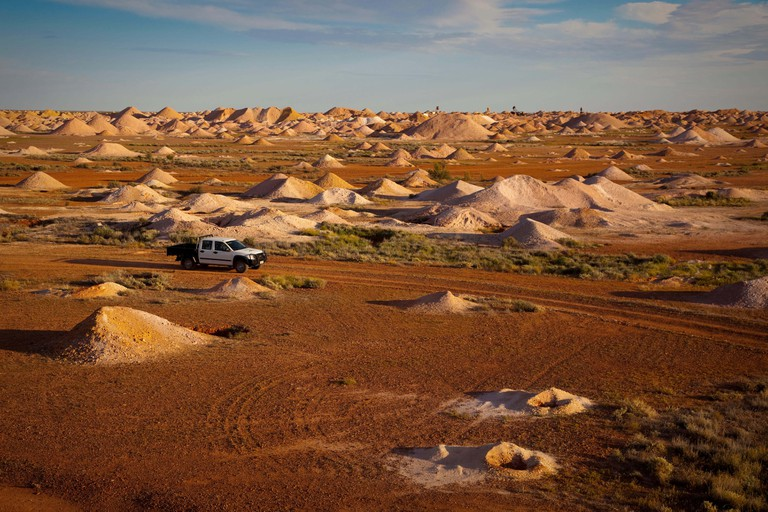 A truck passes between spoil heaps left by opal miners in Coober Pedy, South Australia