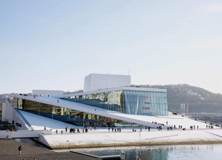 tourists walk around the Oslo Opera House exterior