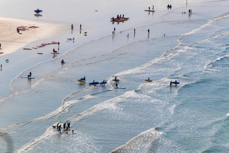 Surfers take to the surf at Saunton Sands, near Croyde, North Devon, England UK