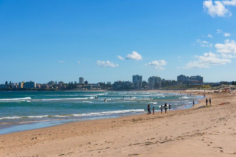 People jogging, sunbathing and swimming, enjoying beach holiday on Cronulla beach