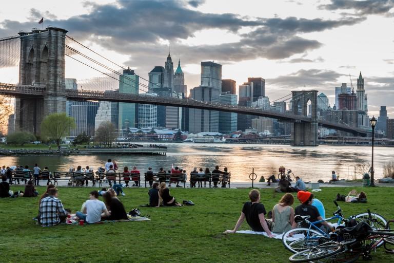 Families friends picnic on East River near Brooklyn Bridge in DUMBO neighborhood NYC