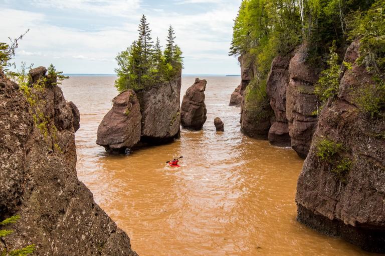 Hopewell Rocks kayaker beach at high tide with kayak, kayaker in water. Bay of Fundy, New Brunswick, Canada