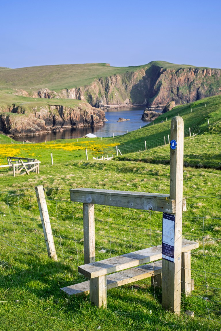 Wooden stile crossing on fence along the spectacular coastline with sea cliffs and stacks at Westerwick, Mainland, Shetland Islands, Scotland, UK