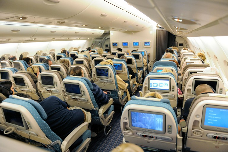 passengers sitting in the economy-class cabin seats of a Singapore Airlines SIA Airbus A380-800 enroute SIN-LHR flight-number SQ322
