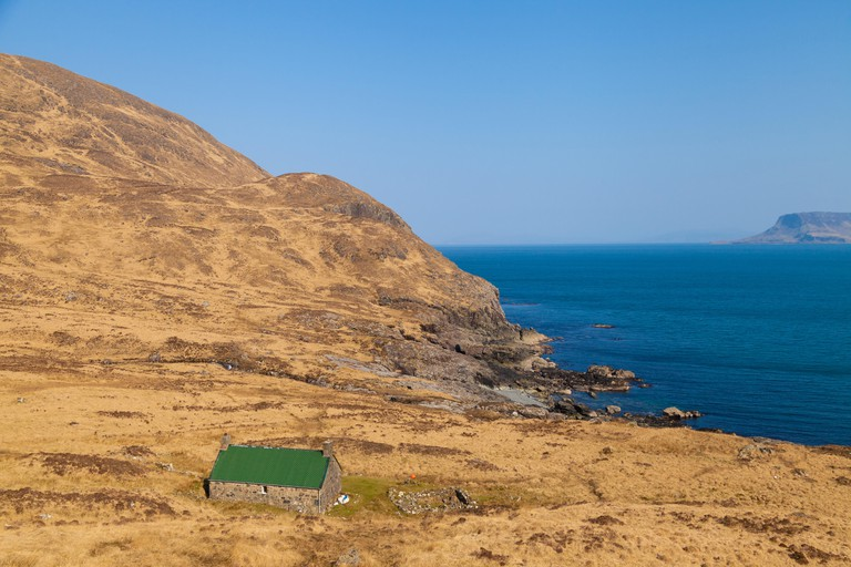 Dibidil Bothy on the Isle of Rum with a glimpse of the Isle of Eigg Scotland.