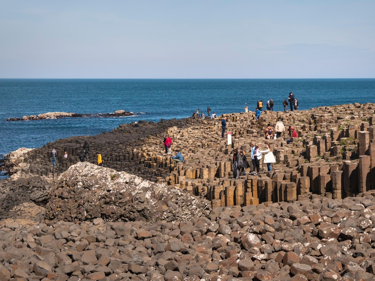 People climb on the rocks of the famous Giants Causeway in Northern Ireland - BUSHMILLS. UNITED KINGDOM - MAY 12, 2019