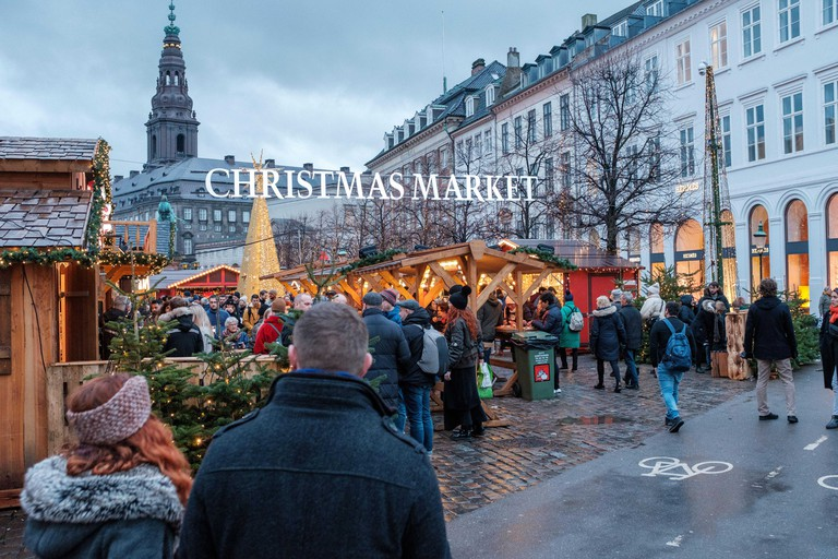 Two people walk towards a Christmas Market in Copenhagen, Denmark
