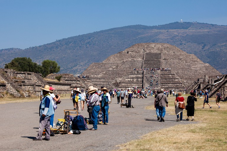 2019-11-25 Teotihuacan, Mexico. View of the pyramid of the moon, against the backdrop of the mountain, tourists climb to the top.