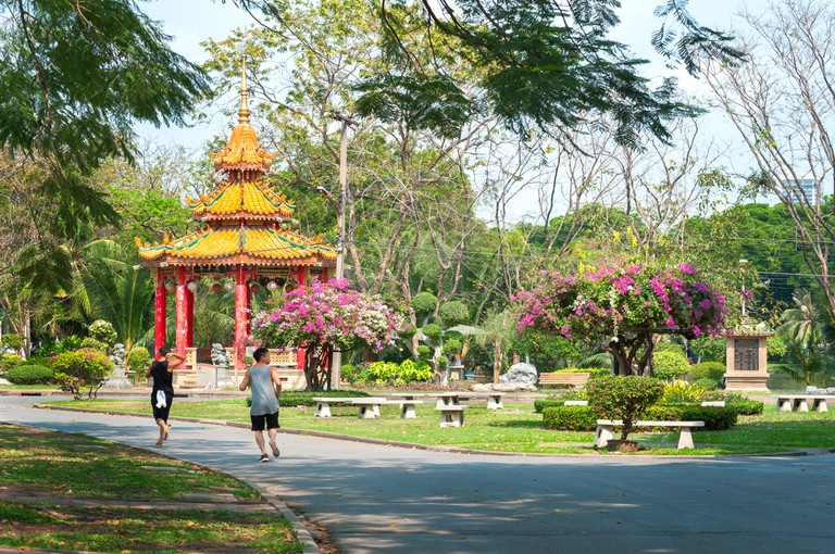 Two male runners run past the Chinese pavilion in Lumpini Park, Bangkok
