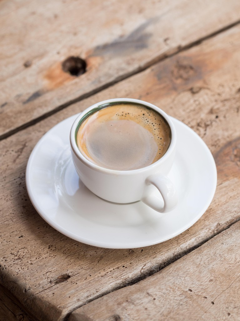 Double espresso in a white cup placed over a dhow wood table. Elevated view, vertical orientation.