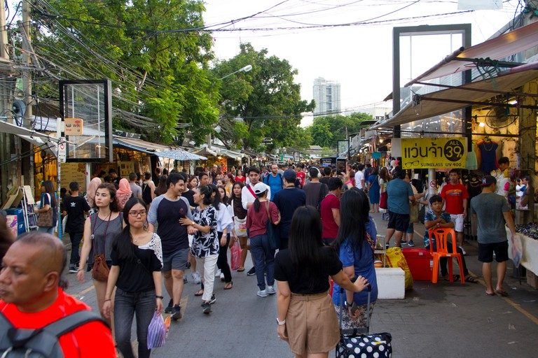 People walk through and shop at Chatuchak weekend market in Bangkok.