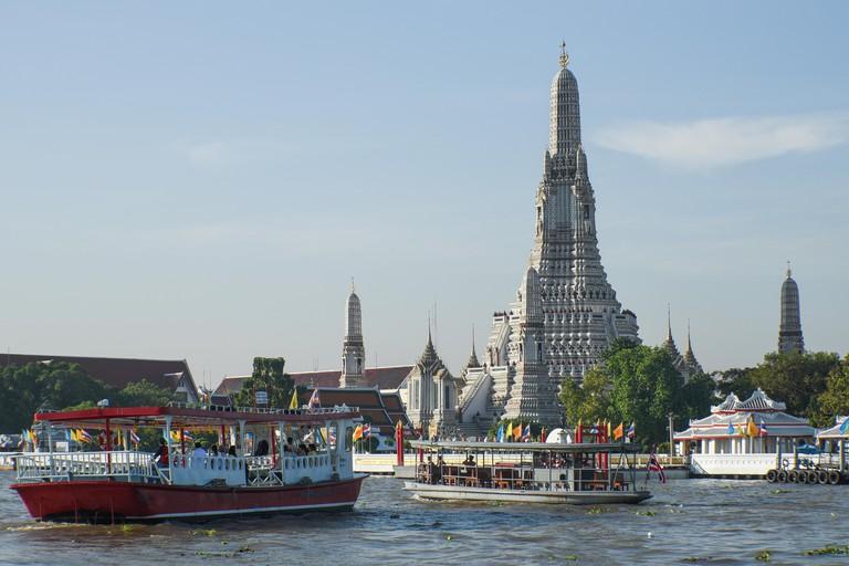 Wat Arun pagoda near Chao Phraya river with many ferries on the river.