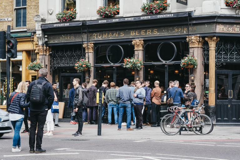 London, UK - June 15, 2019: People standing and drinking outside The Ten Bells pub in Shoreditch, East London. The pub is famous for its supposed asso