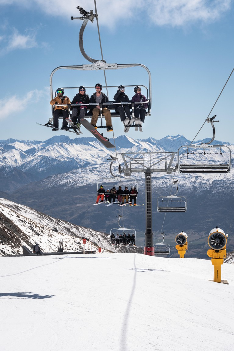 Queenstown, New Zealand - September 7 2019: Skier and snowboarder ride a chairlift in the Remarkables ski resort in New Zealand