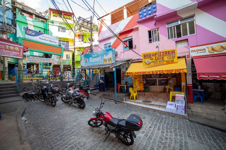 Colourful main square of the favela Santa Marta (Dona Marta) in Rio de Janeiro with motorcycles in the foreground and shops in the background