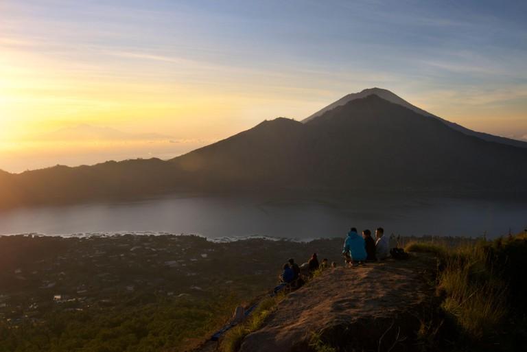 Hikers gathering on the caldera rim of Mount Batur for sunrise, Bali, Indonesia. Lake Batur below.