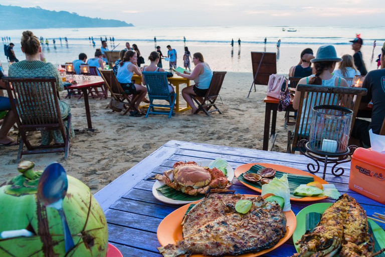 Bali, Indonesia - May 12, 2017: Jimbaran tropical beach is a main popular balinese attraction, famous for the clear, aqua blue water and sea food rest