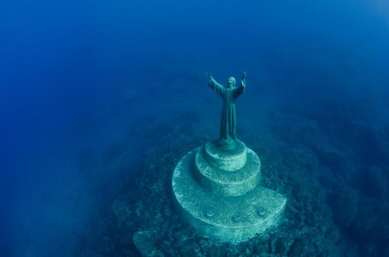 The statue of Christ Of The Abyss (Cristo degli abissi) in the Marine Protected Area of Portofino (Area Marina Protetta, Portofino), Liguria, Italy. Mediterranean Sea. This was the world's first underwater statue, sculpted by Guido Galletti, and placed un