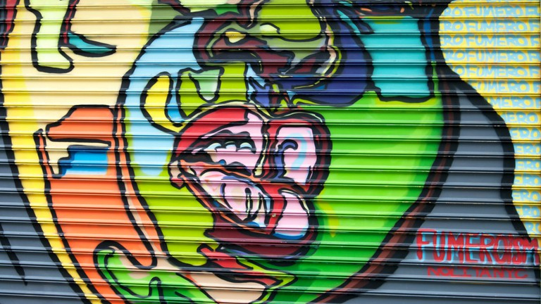 Artists paint onto shop shutters as part of the 100 Gates Project