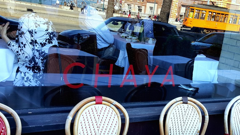 The F Line reflected in the window of Chaya Brasserie