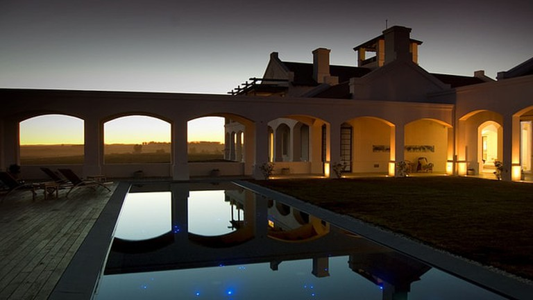 Pool and outside view of Estancia Vik at dusk