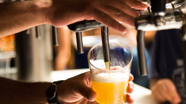 A man pouring a pint of beer from the tap