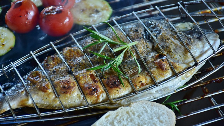 Fish grilling with some vegetables on the side