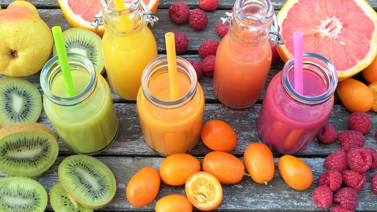 Three fruit smoothies with fruits on a wooden table