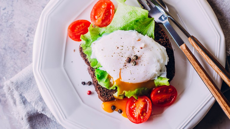 Rye bread toast and poached egg with green salad and cherry tomatoes