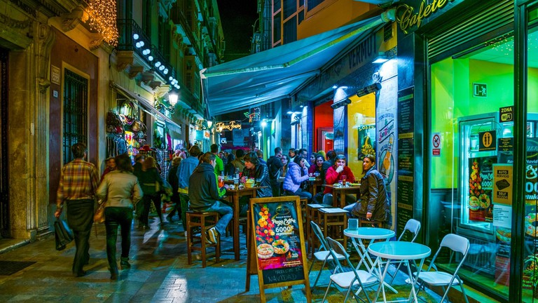 Crowds of tourists are strolling through the historical center of malaga after sunset