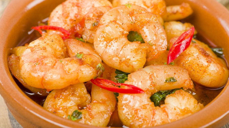 Gambas Pil Pil (Sizzling prawns with chili and garlic).