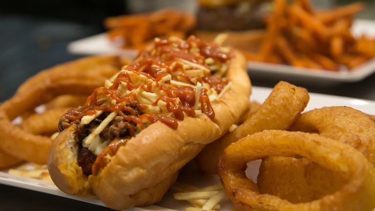 Spice up your gourmet dog with a little sriracha sauce and an order of onion rings on the side