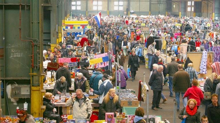 People shop at the indoor secondhand and vintage flea market in the IJ Hallen, Amsterdam