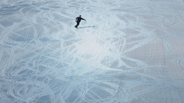 Lone Snowboarder cruising on a Connecticut Slope with grooming patterns.