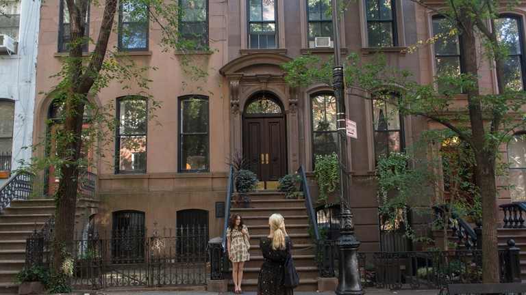 Tourists taking photos outside the famous 66 Perry Street, Brownstone in Greenwich Village, Manhattan where Carrie Bradshaw (Sarah Jessica Parker) lived in the series.
