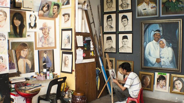 A Malaysian artist working on a painting at Annexe Central Market, Kuala Lumpur, Malaysia.
