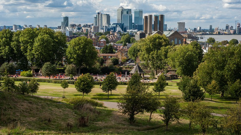 The financial district of Canary Wharf in London under dramatic sky seen from Greenwich Park.