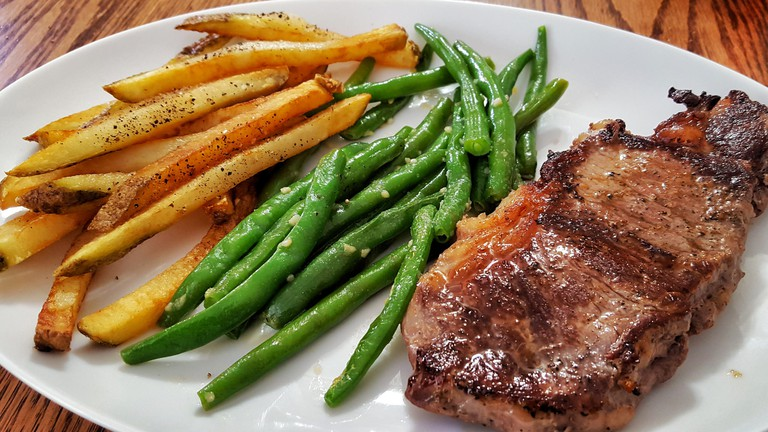 Rib eye steak with fries and garlic butter green beans