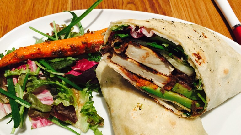 Vegan wrap filled with tofu, sweet potato, and greens.