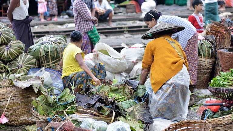 A market overflows with fresh produce near train tracks in Myanmar